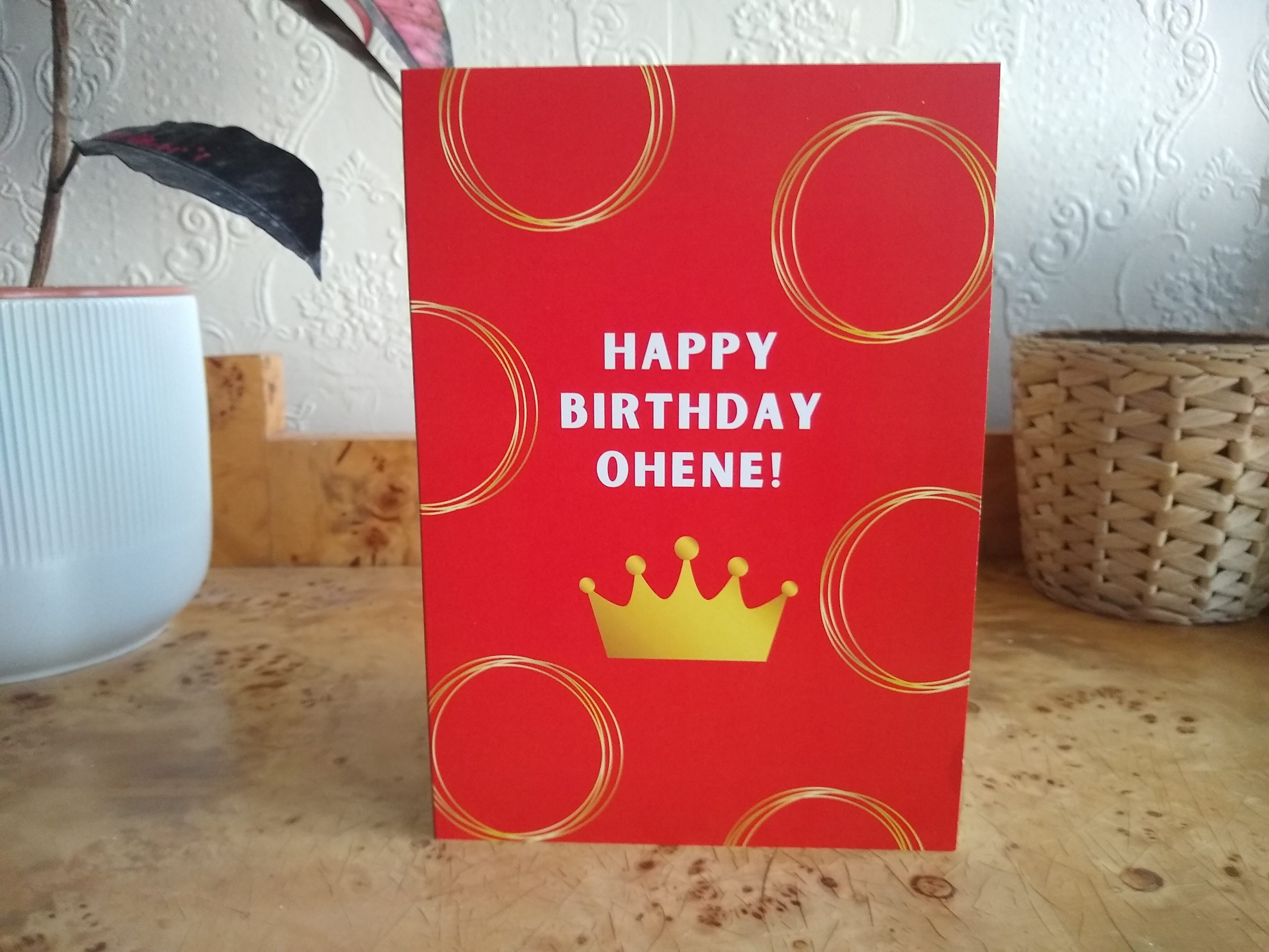 Happy Birthday Ohene written in gold on a red background with a gold crown underneath and gold circles all over the card